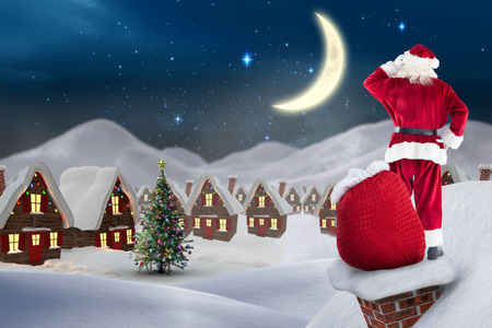 christmas village: Santa on cottage roof  against cute christmas village at night Stock Photo