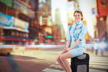 hotesse de l air: Pretty air hostess smiling at camera against blurred new york street Banque d'images