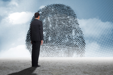 thumbprint: Businessman turning his back to camera against thumbprint graphic over desert