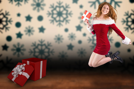 pere noel sexy: Festive redhead jumping with gift against snowflake wallpaper over floor boards