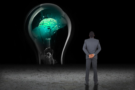 hands behind back: Young businessman standing with hands behind back against glowing brain in light bulb