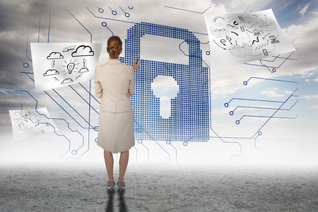 business security: Thinking businesswoman against circuit board lock grapic in desert Stock Photo