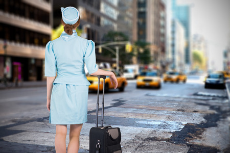 hotesse de l air: Pretty air hostess leaning on suitcase against new york street