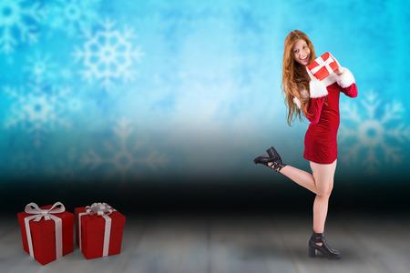pere noel sexy: Rousse Festive tenant un cadeau, sur fond de flocon de neige au-dessus de plancher