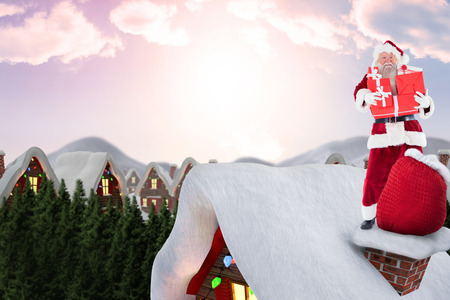 santas village: Santa on cottage roof  against cute village in the snow Stock Photo