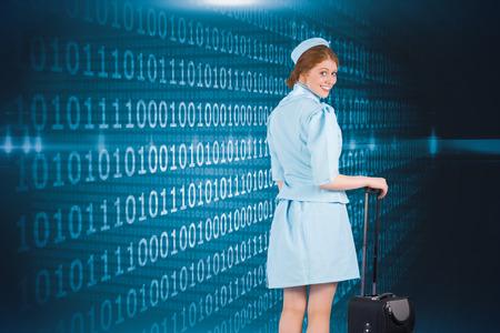 hotesse avion: Jolie h�tesse de l'air se penchant sur valise contre bleu brillant code binaire sur fond noir