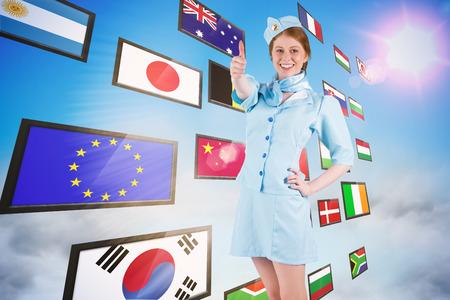 hotesse avion: H�tesse de l'air jolie main sur la hanche contre collage d'�cran montrant des drapeaux internationaux Banque d'images