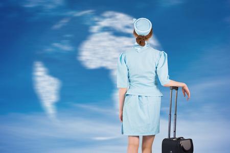 hotesse avion: Jolie h�tesse de l'air se penchant sur valise contre globe g�n�r� num�riquement dans le ciel