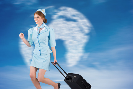hotesse avion: Pretty air hostess pulling suitcase against digitally generated globe in sky Banque d'images