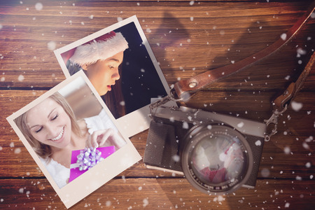 christmas memories: Composite image of christmas memories against instant photos on wooden floor