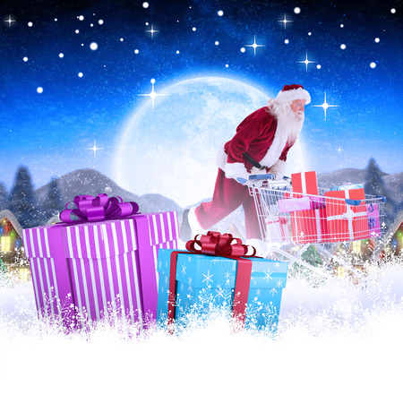 pushes: Santa pushes a shopping cart against quaint town with bright moon Stock Photo