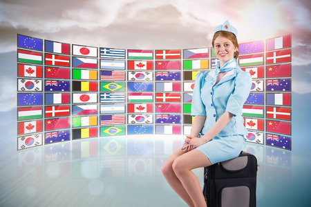 international flags: Pretty air hostess smiling at camera against screen collage showing international flags