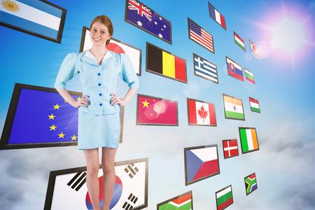 hotesse avion: Jolie h�tesse de l'air souriant � la cam�ra contre collage d'�cran montrant des drapeaux internationaux