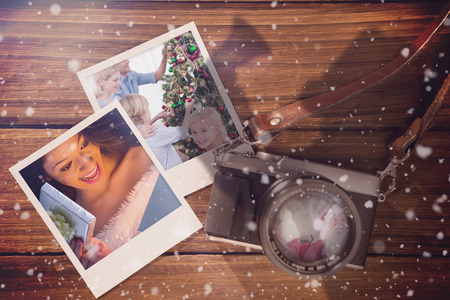 in memory: Composite image of christmas memories against instant photos on wooden floor