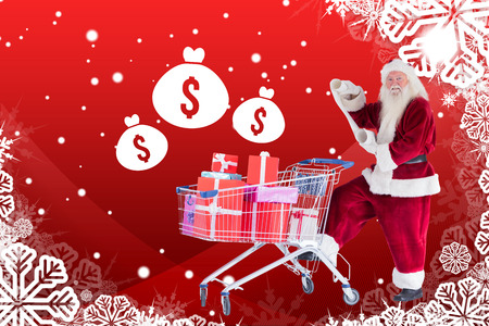 pushes: Santa pushes a shopping cart while reading against christmas themed snow flake frame Stock Photo