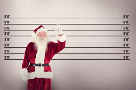 father in law: Jolly Santa waving at camera against mug shot background Stock Photo