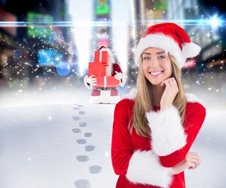 adult footprint: Pretty santa girl smiling at camera against santa delivering gifts in city Stock Photo