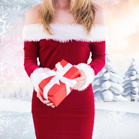 pere noel sexy: Jolie Santa Girl holding gift contre paysage enneigé avec sapins Banque d'images