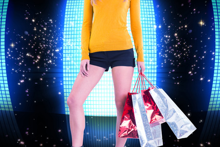 hot pants: Stylish woman with shopping bags against glittering screen on black background