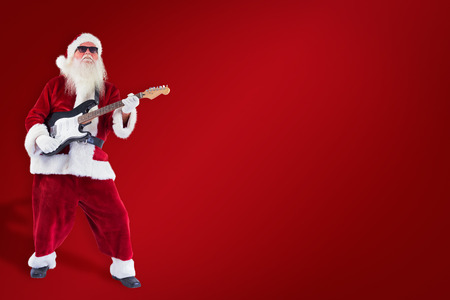 lean back: Santa Claus plays guitar with sunglasses against red background