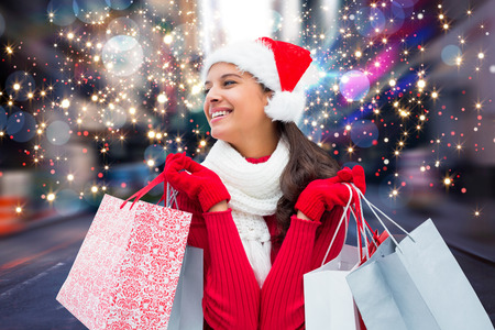 christmas shopping: Festive brunette holding shopping bags against blurry new york street Stock Photo