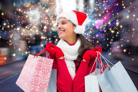Festive brunette holding shopping bags against blurry new york street Foto de archivo