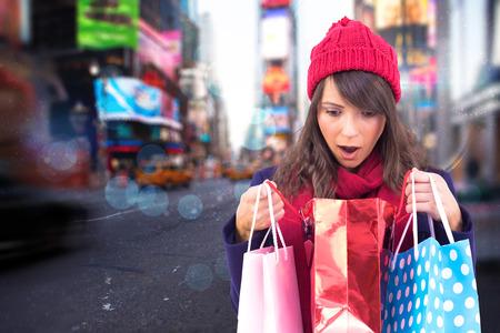 opening gift: Shocked brunette opening gift bag against blurry new york street