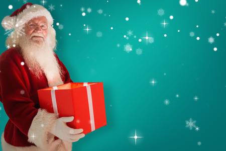 Father christmas holding a gift against red background Stock Photo