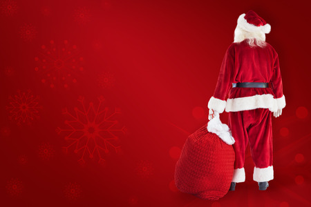 fancy bag: Santa carrying sack of gifts  against red background Stock Photo