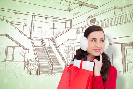 ear muffs: Brunette with ear muffs holding shopping bag full of gifts against maroon christmas tree pattern