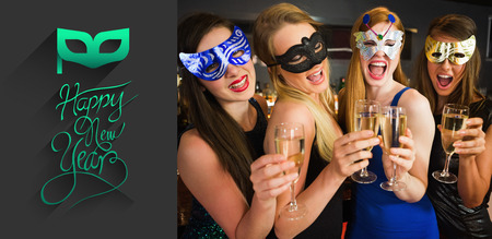 hedonism: Attractive friends with masks on holding champagne glasses against classy new year greeting