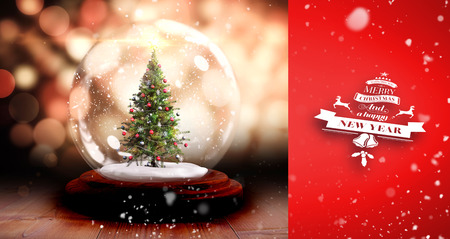 Snow falling against christmas tree in snow globe Stock Photo