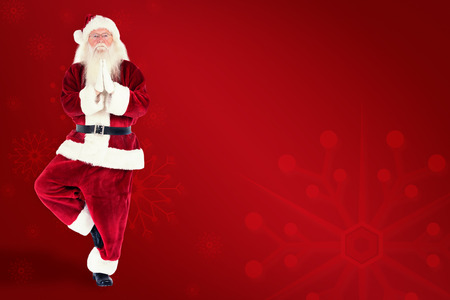 pere noel: Father Christmas doing some yoga against red background Banque d'images