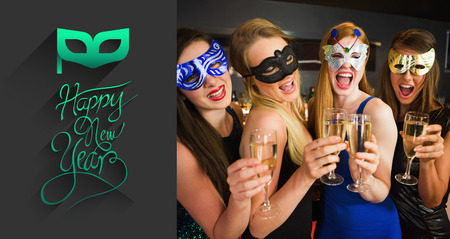 hedonistic: Attractive friends with masks on holding champagne glasses against classy new year greeting