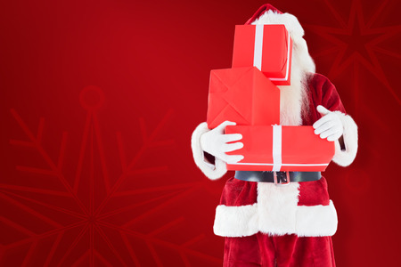 home trainer: Santa covers his face with presents against red background Stock Photo