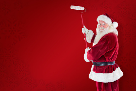 pere noel: Father Christmas paints a wall against red background