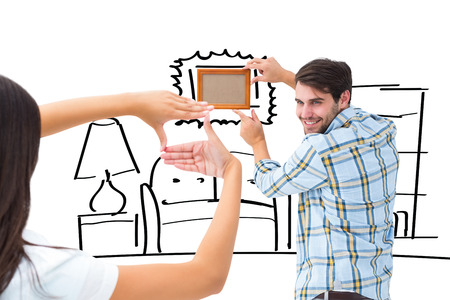 putting up: Happy young couple putting up picture frame against living room sketch