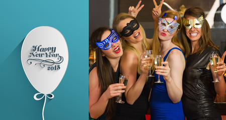 hedonistic: Attractive women wearing masks holding champagne against classy new year greeting Stock Photo