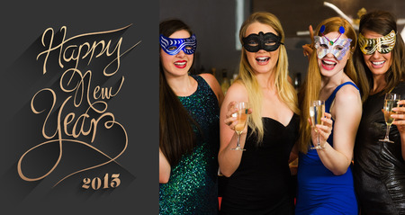 hedonism: Laughing friends wearing masks holding champagne glasses against classy new year greeting