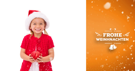 wearing santa hat: Cute little girl wearing santa hat holding bauble against orange vignette
