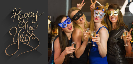hedonism: Attractive women wearing masks holding champagne against classy new year greeting Stock Photo