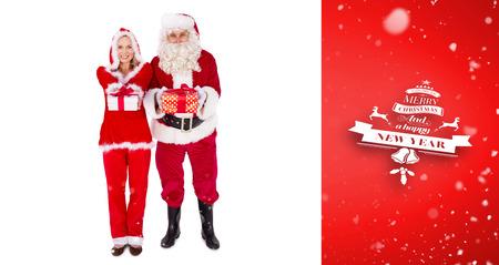 mrs: Santa y se�ora Claus sonriendo a la c�mara regalo de ofrecimiento contra la vi�eta roja
