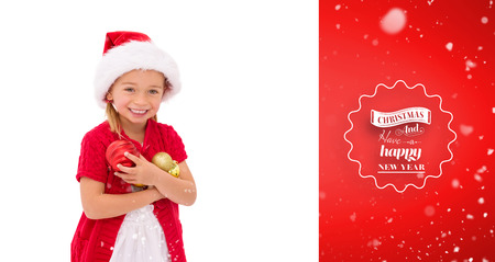 wearing santa hat: Cute little girl wearing santa hat holding baubles against red vignette
