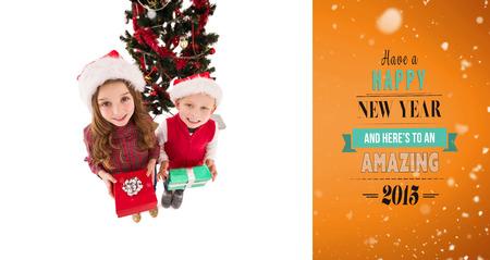 siblings: Festive little siblings smiling at camera holding gifts against orange vignette
