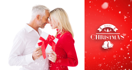 wrapped gift: Smiling couple passing a wrapped gift against red vignette