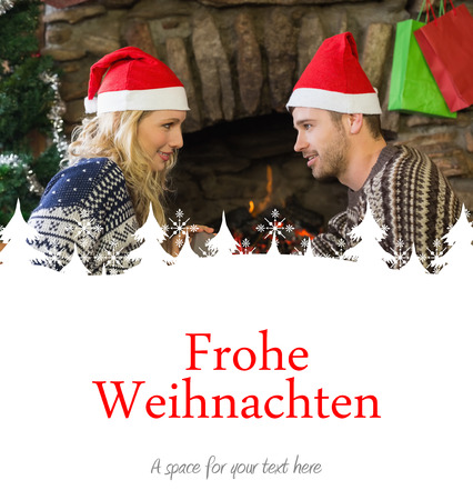 gifting: Man gifting woman in front of lit fireplace during Christmas against christmas greeting in german Stock Photo