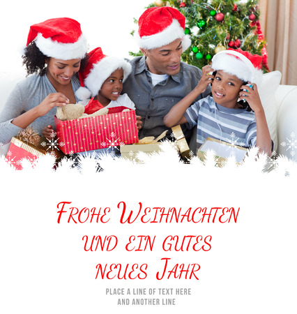 weihnachten: Happy family playing with Christmas presents against frohe weihnachten message
