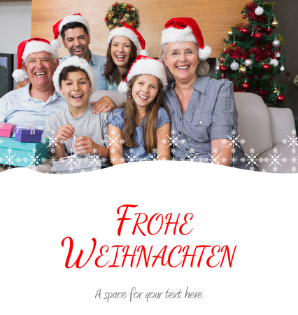 frohe: Extended family in Christmas hats with gift boxes in living room against christmas greeting in german Stock Photo