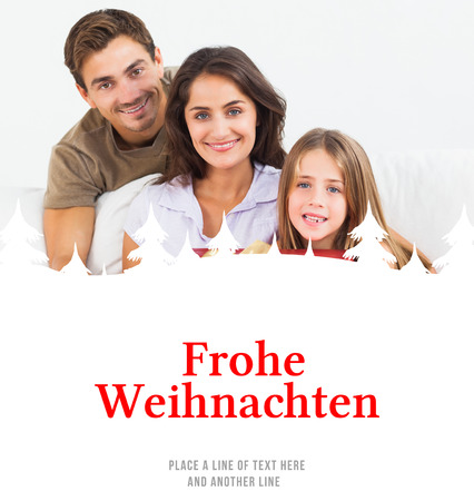 frohe: Parents offering a gift to their daughter against christmas greeting in german