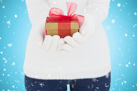 white gloves: Woman in white gloves holding gift against blue vignette Stock Photo